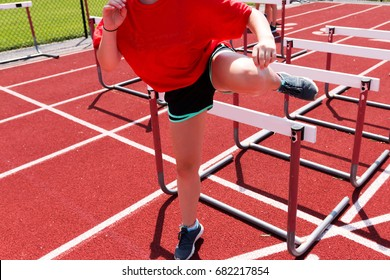 A female high school runner is doing hurdle drills on a red track outside on a sunny day