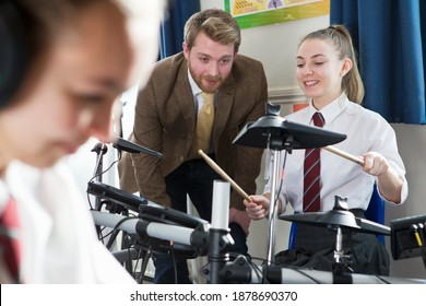 Female high school student playing drums during a music class with a teacher watching her.