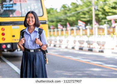 Female high school student is standing on the roadside and wait for going back home by school bus, Thailand, southeast Asia.