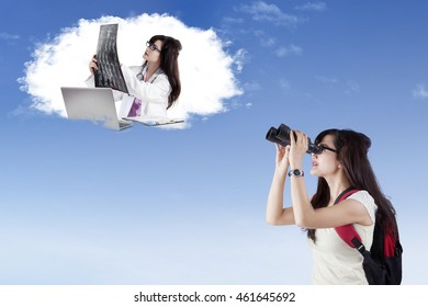 Female high school student using binoculars to look at her future job as a doctor