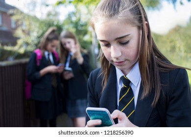 Female High School Student Wearing Uniform Being Bullied Online By Girl Pupils