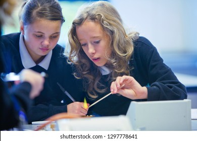 Female high school students using Bunsen burner in science class