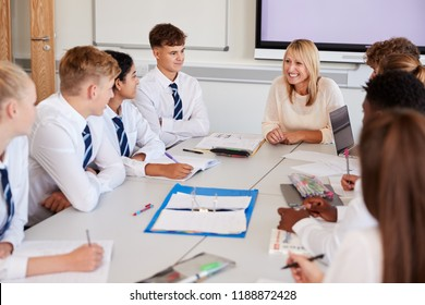 Female High School Teacher Sitting At Table With Teenage Pupils Wearing Uniform Teaching Lesson