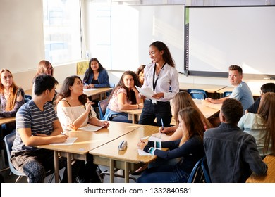 Female High School Teacher Standing By Student Table Teaching Lesson