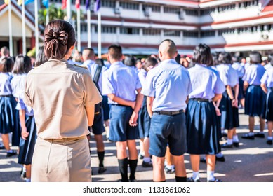 Female high school teacher in Thai government teacher uniform is standing among students, Thailand, southeast Asia.