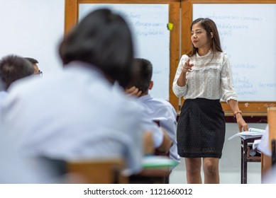 Female high school teacher wrote her lesson on white board and teach her students in classroom, Thailand, southeast Asia.