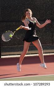 Female High School Tennis Player Hits Forehand Shot
