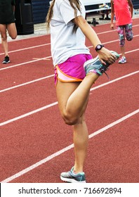 A female high school track runner teaching middle school girls how to stretch before practice.