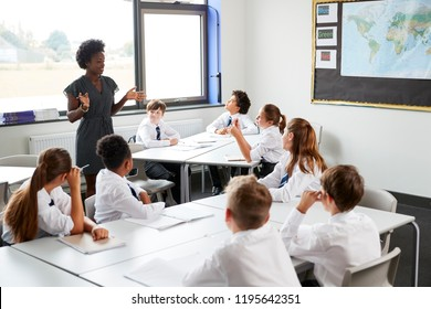 Female High School Tutor Standing By Tables With Students Wearing Uniform Teaching Lesson
