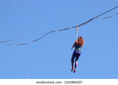 Female highliner on a rope. Extreme sport on the nature. Balancing on the sling. Equilibrium at altitude.