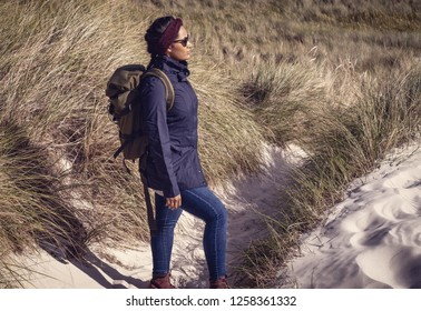 Female hiker with backpack in the dunes of Amrum Germany.