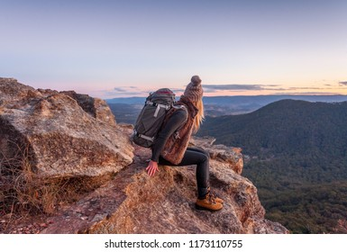 Female hiker with backpack rests on a mountain peak rocky ledge with magnificent views in Blue Mountains Australia