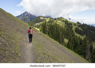 A female hiker with backpack walking away from the camera on the Klahhane Ridge trail at Olympic National Park in Washington.