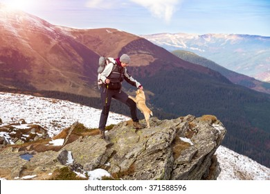 Female Hiker with Backpack and walking Poles staying at rocky Mountains Cliff and playing with accompanying Dog Scenic view with green Hills and Sky on Background