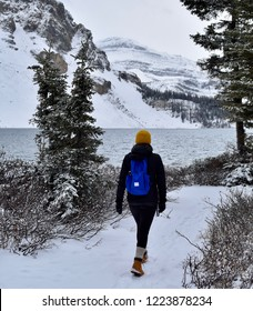 Female hiker with bright blue backpack and yellow toque hiking along glacial lake in the Canadian Rockies