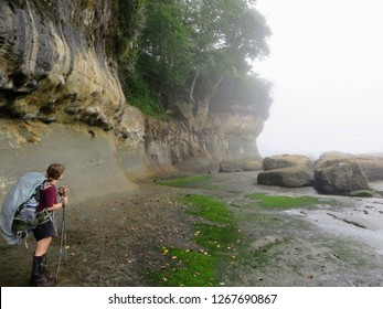 A female hiker carefull navigating the coast line along the West Coast Trail Hike on the shores and forests of Vancouver Island, British Columbia, Canada.  The mist creates a mysterious atmosphere