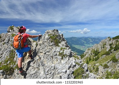 Female hiker climbing at an exposed ridge close to the village Oberstdorf in the Allgau Alps, Bavaria, Germany. Alpine landscape with rocky mountains, forests and blue sky.
