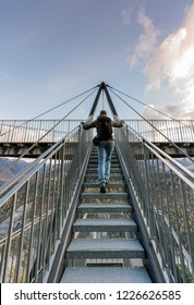 female hiker climbing up metal stairs that  lead up to an impressive lookout and viewpoint platform in the Grisons near Flims in Switzerland under a blue sky with white clouds