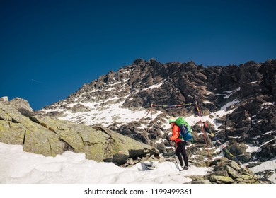 Female hiker climbing up to the mountain top in winter. Rysy. Slovakia.