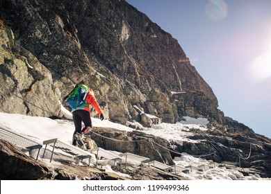 Female hiker climbing up on ladder to the mountain top in winter. Rysy. Slovakia.