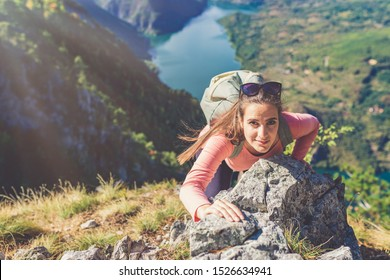 Female hiker climbing a rock on a hill above beautiful river valley. Healthy lifestyle and nature concepts.