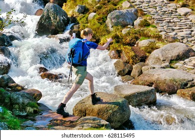 Female hiker crossing a small mountain stream on stepping stones