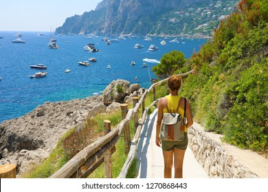 Female hiker descent the pathway with spectacular landscape of Capri, Naples, Italy