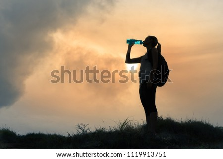 Female hiker drinking bottle of water.