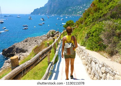 Female hiker go down and descent the pathway with spectacular landscape of Capri, Naples, Italy