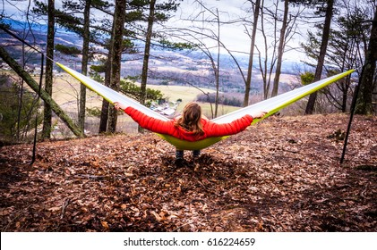 Female hiker hanging out in a hammock looking out at the scenic view