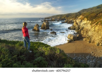 A female hiker looks out over the coastline of Big Sur, California.