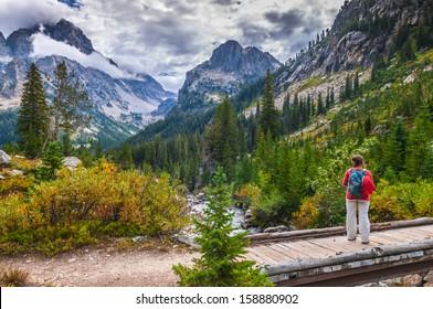 Female Hiker on a foot bridge in Cascade Canyon