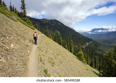 A female hiker on a narrow mountain ridge with a hiking pole, walking away from the camera.