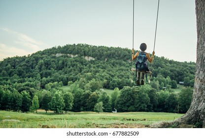 A female hiker is on a swing in the forrest with mountain views.