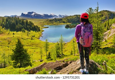 A female hiker overlooking the iconic peaks of the Canadian Rocky Mountains at Sunshine Meadows, Banff National Park, Alberta Canada.