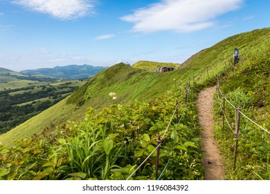 A female hiker pauses to look at wildflowers and the vast mountain scenery at the Rebun Island Edelweiss Colony viewpoint in Hokkaido, Japan