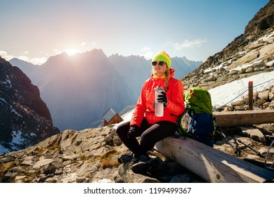 Female hiker quench thirst after climbing in the winter mountain and rest. Rysy. Slovakia.