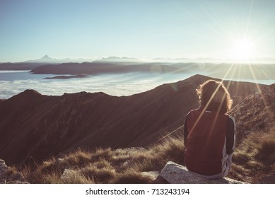 Female hiker reaching her goal at the mountain top and looking at majestic panoramic view of the Alps. Wide angle view at sunset in backlight, toned image, vintage filter, split toning.