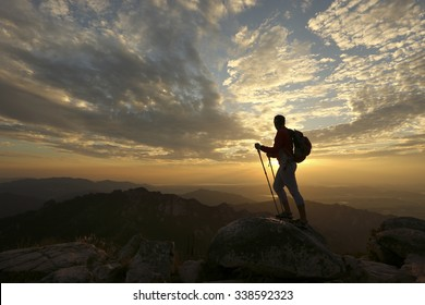 Female hiker reaching the summit of a mountain and watching the sun set over a beautiful landscape with an orange  sky silhouetting her in a dramatic way.
