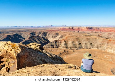 Female hiker sitting on the edge of Muley Point overlook with panoramic view of the desert between Utah and Arizona, USA