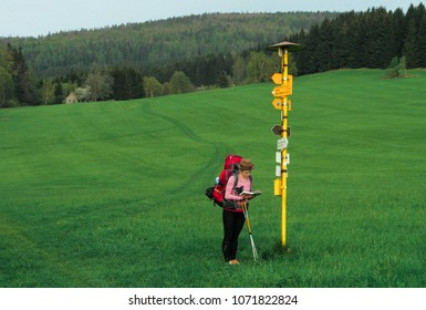 female hiker standing next to a hiking trail signpost, looking into the map to find direction