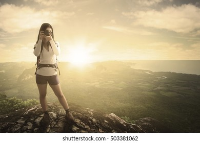 Female hiker standing on the rock while taking pictures and looking at the camera with valley view