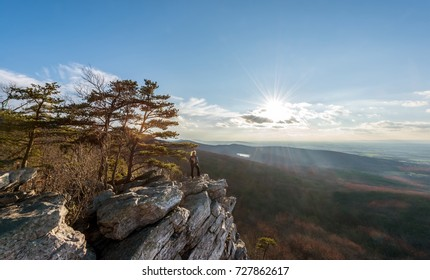 Female hiker standing in the wind at the edge of a rocky cliff on the summit of an Appalachian mountain enjoying the sunset and vista