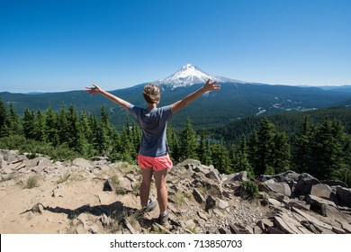 Female hiker stands on the summit of Tom Dick and Harry Mountain in Mt. Hood National Forest, with her arms held up, looking at Mount Hood.