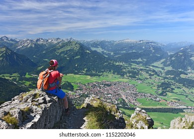Female hiker at the summit of Rubihorn mountain enjoying the view to the village Oberstdorf and the Allgau Alps in the border region of Germany and Austria. Alpine landscape under blue sky