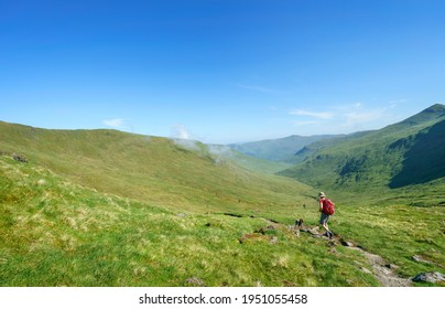 A female hiker walking along a mountain path to the summit of Meall Corranaich with the glen of Allt a Chobhair and the summit of Carn Gorm in the distance in the Scottish Highlands, UK landscape.