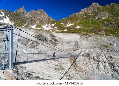 Female hiker walking on the hanging bridge over the Glacier de Corbassiere on a mountain trail around Valais Swiss Alps.
