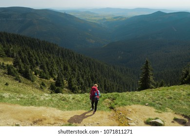 female hiker walking on a trail on highlands, jeseniky mountains, czech republic