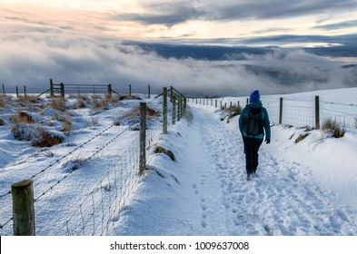 Female Hiker walking on a Winter evening at sunset. Peak District National Park, Derbyshire, England, UK. Snow covered path and fields on the route from Kinder Scout to Hayfield.