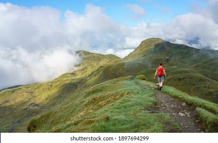 A female hiker walking over the narrow mountain ridge of the summit of Meall Garbh towards Beinn Nan Eachan near Loch Tay in the Scottish Highlands, UK mountains.